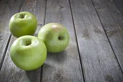 Apples On Wood Background. Three green apples on a rustic wood background. Can be used with similar image no.27312759 and 27312817 Royalty Free Stock Photography