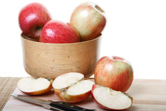 Whole and Cut Apples on Board. Apples in a wood bowl and on cutting board with some cut in half Royalty Free Stock Image