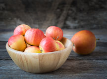 Apples in a wood bowl on wooden background. Royalty Free Stock Images