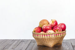 Apples in wooden basket on wooden floor Royalty Free Stock Photo