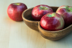 Apples in the wooden heart shape plate on the table Royalty Free Stock Image