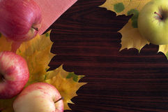 Apples. On a wooden table surrounded by fallen leaves Stock Photography