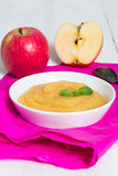 Applesauce on pink paper and spoon Stock Photos