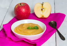Applesauce on pink paper and spoon Stock Photo