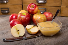 Applesauce on a wooden table. Apple sauce dessert (stewed apple) on a wooden table with whole apples around Royalty Free Stock Image