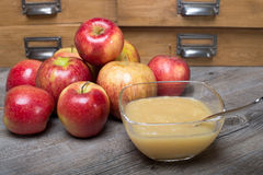Applesauce on a wooden table. Apple sauce dessert (stewed apple) on a wooden table with whole apples around Stock Photos