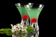 Appletini - Most popular cocktails series. Appletini cocktail in contemporary martini glass over black background garnished with maraschino cherry, and apple stock photos
