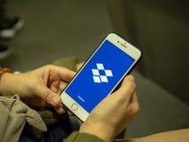 Appli mobile s'ouvrant de Dropbox de femme avec le logo sur l'écran d'iPhone tout en permutant sur le métro image stock