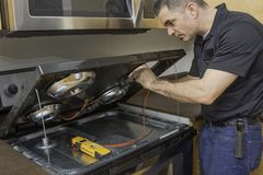 Appliance technician checking a stovetop range Royalty Free Stock Photos