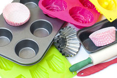 Appliances for baking closeup on white background. Silicone and metal molds for cakes and cookies, paper cups, rolling pin dough krtspnym up on a white Stock Images