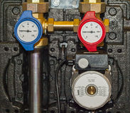 Appliances hot and cold water. Water pump, thermometers, hot and cold water pipes are installed on Stock Images