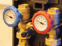Appliances hot and cold water. Water pump, thermometers, hot and cold water pipes are installed on stock photography