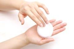 Applicandosi crema per le mani alle mani Immagine Stock