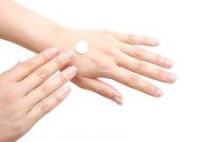Applicandosi crema per le mani alle mani Fotografia Stock