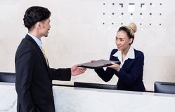 Applicant giving his documents to receptionist Stock Image