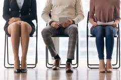 Applicants waiting for job interview, sitting on chairs and prep. Three candidates for position waiting for their turn in job interview sitting on chairs Royalty Free Stock Photo
