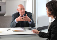 Application. Young businesswoman sitting in front of a senior manager and talking Stock Image