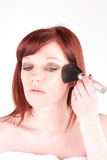 Application. Woman using a blusher brush getting ready for a night out Stock Photography