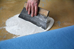 Application of adhesive for the carpet. A floor fitters at work royalty free stock photography