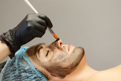 Application of carbon nanogel. The cosmetologist applies the carbon nanogel to the skin of the client`s face. Preparation for laser treatment of the skin. Carbon Royalty Free Stock Photography