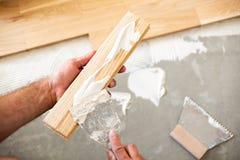 Application de la colle de parquet d'un plat de plancher photo stock