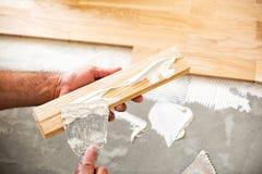 Application de la colle de parquet d'un plat de plancher images libres de droits