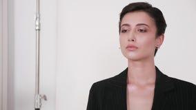 Application des contacts finaux sur le visage modèle sur l'ensemble professionnel de studio de mode clips vidéos