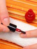 Application du vernis à ongles rouge, ongles manucurés de femme images stock