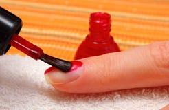 Application du vernis à ongles rouge, ongles manucurés de femme photos libres de droits