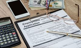 Application for employment with money, calculator. Pen on desk Royalty Free Stock Photos