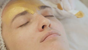 Application of golden masks on the face of the model. Close up. Full HD stock footage