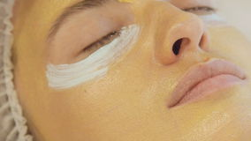 Application of golden masks on the face of the model. Close up. Full HD stock video footage