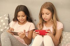 Application for kids fun. Internet surfing and absence parental advisory. Smartphone internet access. Girls sisters wear. Pajama busy with smartphones. Children royalty free stock images