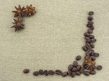 Square cut out from rassypanyh beans roasted coffee and anise flowers on rough canvas beige. Stock Photos