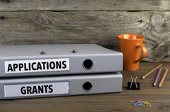 Applications and Grants - two folders on wooden office desk Stock Photos