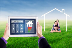 Applications of smart home controller on tablet. Hands holding a digital tablet with smart home controller applications on the screen. Shot with happy children Stock Image