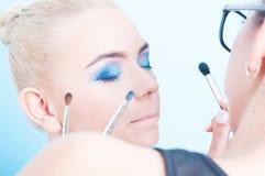 Applicazione del trucco colorato professionista sulla bella ragazza fotografia stock