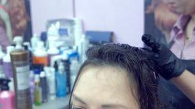 Applicazione della cheratina ai capelli con una spazzola Rafforzamento dei capelli con la cheratina video d archivio
