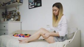 Applicazione della crema del moisturizer Giovane donna graziosa che si preoccupa per le sue gambe che si siedono sul letto archivi video
