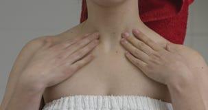 Applicazione della crema sul collo della donna archivi video