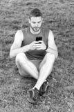 Applicazione di messa a punto Lo sportivo con lo smartphone ed il pedometro preparano per il trotto Come itinerario di messa a pu fotografia stock