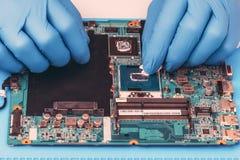 Applicazione di pasta termica sul chip di unit? di elaborazione del computer portatile per il raffreddamento di alta qualit? immagini stock