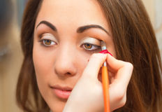 Applicera ögonskugga på ögonlocket Arkivbild