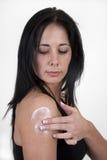 applicera armkräm henne som moisturizing till kvinnan Arkivfoto