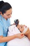 applicera beauticianansiktsbehandlingmaskeringen Royaltyfri Fotografi