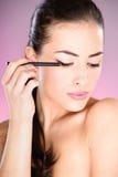 applicera den kosmetiska ögonblyertspennakvinnan Royaltyfri Bild
