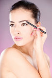 applicera den kosmetiska ögonblyertspennakvinnan Arkivfoton
