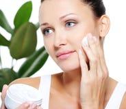 applicera den kräm- fuktighetsbevarande hudkrämkvinnan Royaltyfri Foto