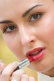 applicera den nätt sinnliga kvinnan för skönhetsmedel Arkivfoto