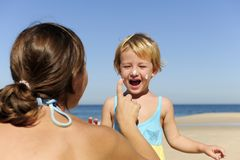 applicera det lyckliga barnet henne modersunscream till Arkivbilder
